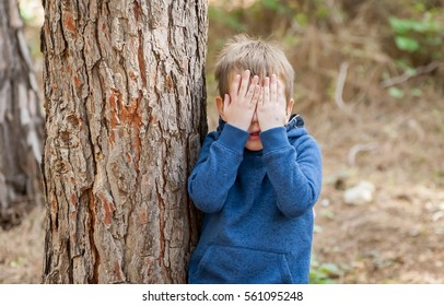 Little Caucasian boy closing his face with hands as if playing hide and seek or scared of something. Hiding face. Closed face. Autism, autistic child, aspergers, asperger's disorder, autistic boy