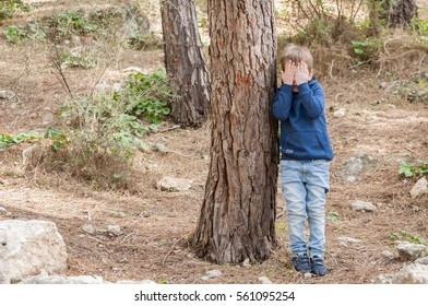 Little Caucasian boy closing his face with hands as if playing hide and seek or scared of something. Asperger syndrome, asperger's disorder, autism, autistic child, social behavior.
