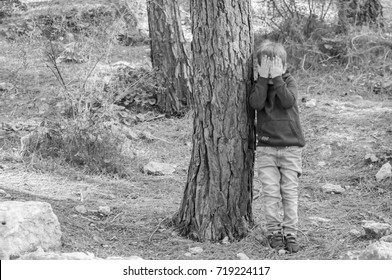 Little Caucasian boy closing his face with hands as if playing hide and seek or scared of something. Asperger syndrome, asperger's disorder, autism, autistic child, social behavior black and white