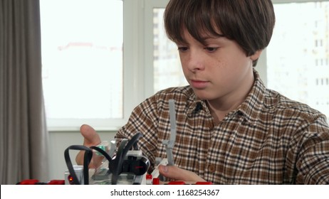 Little caucasian boy discourages by toy vehicle assembling. Close up of brunette male kid putting his hand on his cheek. Camera tilting down from child's face to the piece of construction set on the