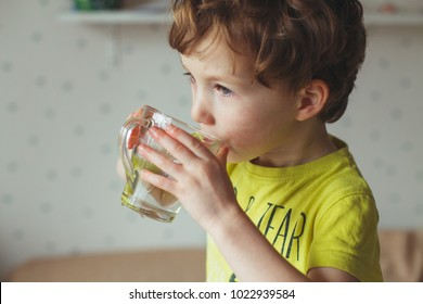 Little caucasian boy drink water in glass at home. Cute curly toddler is drinking water. Health and water concept