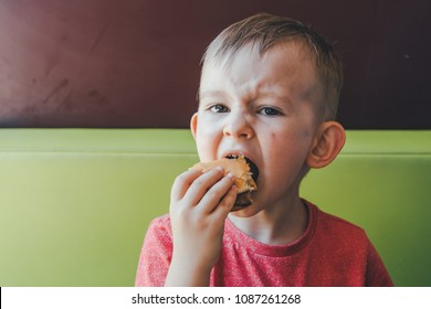 little caucasian boy eating burger, looking down