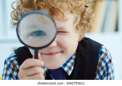 Little Caucasian boy looking at camera through magnifying glass in classroom. Studying the microworld with tools.