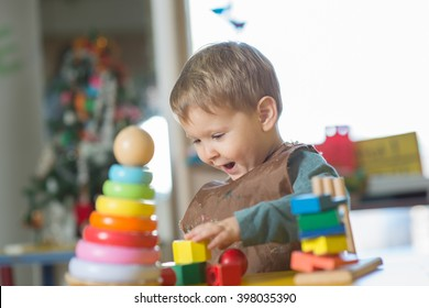 Little caucasian boy plaing with Montessori toy in pre-school