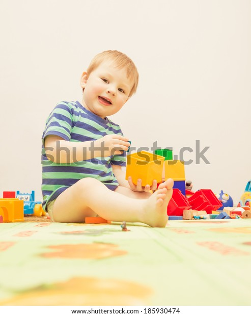 little caucasian boy playing with toys indoor