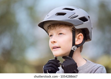 little caucasian boy putting bike helmet on, safety concept