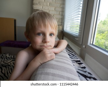 Little Caucasian boy is sitting on the sofa near the window
