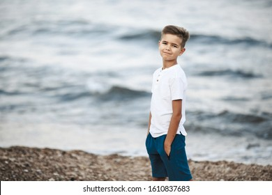 Little caucasian boy is standing on the beach near the wavy sea dressed in white t-shirt and blue shorts