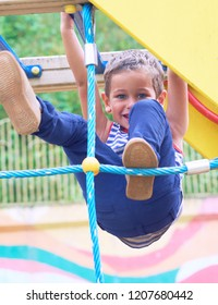 Little Caucasian boy in striped t-shirt hang the blue bar by his hand to exercise at out door playground in summer day.
