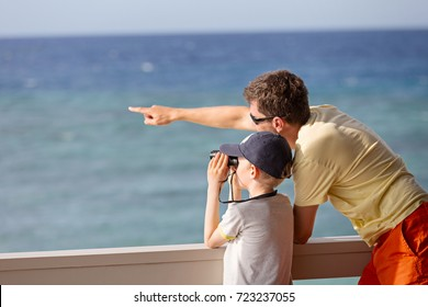 little caucasian boy using binoculars and his young father pointing with finger and showing something, exploration and vacation concept