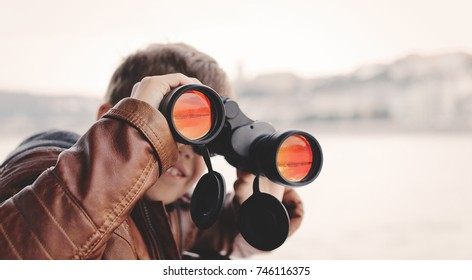 Little caucasian boy watching, looking, gazing, searching for by binoculars during trip toothy smile