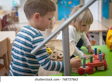 Little caucasian brother and sister playing with wooden toys