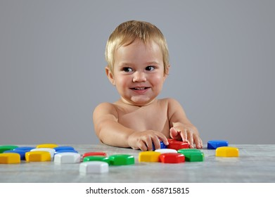Little caucasian child playing with lots of colorful plastic blocks lying on the table. Early school