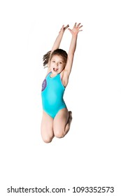 Little caucasian female 7 years old girl in cyan swimming costume jumping on white background. Summertime, sport, springboard diving and recreation concept.