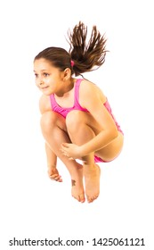 Little caucasian female 8 years old girl in pink swimmwear jumping on white background. Summertime, sport and recreation concept.