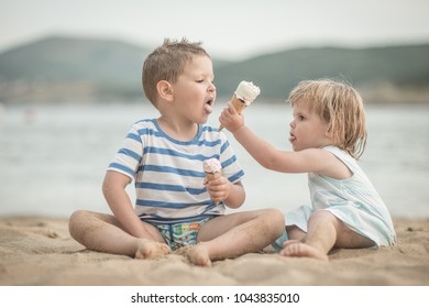 Little caucasian gilr giving ice cream to her brother at sandy beach