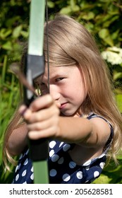 little caucasian girl aiming arrow from big bow on green garden outdoor background