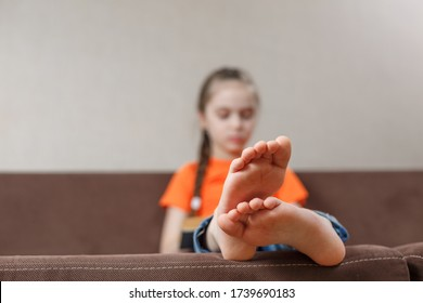 A little caucasian girl with bare feet reading book while sitting on a sofa at home. Foot closeup. selective focus
