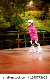 A little caucasian girl beginner roller in the autumn park in the rainy day. Rollerblading and outdoor activity concept