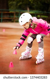 A little caucasian girl beginner roller falling on the ground. Rollerblading and outdoor activity concept
