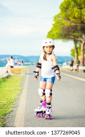 A little caucasian girl beginner roller . Summer evening on the seaboard, the bicycle path of Koper, Slovenia