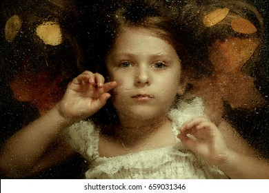 Little caucasian girl, close up portrait  across a water drops on glass, with autumn leaves in background. Emotional portrait, autumn concept