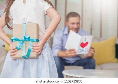 Little caucasian girl daughter congratulate daddy hiding giving a surprise card and gift box. Family holiday father and girl celebrate together. Love lifestyle happy father's day holiday party concept