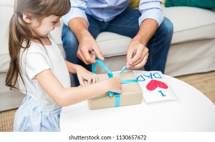 Little caucasian girl daughter congratulate daddy giving a surprise card and gift box. Happy family holiday father and girl celebrate together. Love lifestyle unwrap boxing or father's day concept