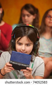 Little Caucasian girl with earphones plays a handheld video game