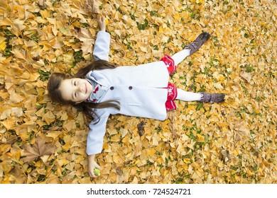 little caucasian girl enjoying sun at beautiful autumn afternoon