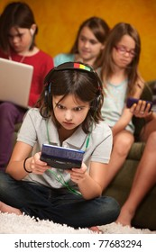 Little Caucasian girl focused on her portable gaming console