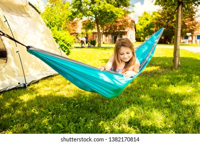 Little caucasian girl in the hammock and the tent in background in the sunny summer day. Summertime and vacation concept.