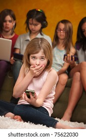 Little Caucasian girl with handheld device covers her mouth