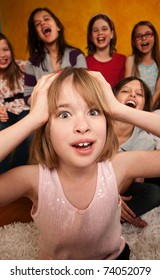 Little Caucasian girl with hands on head while friends laugh