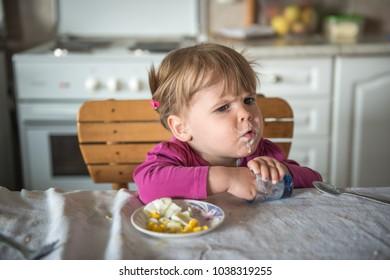 Little caucasian girl have messy breakfast