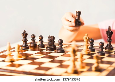 Little caucasian girl holding a black castle in the hand. The chess game. Close-up photo, copy space.