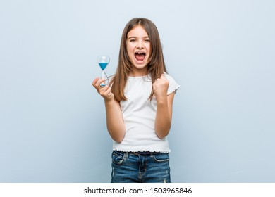 Little caucasian girl holding an hourglass cheering carefree and excited. Victory concept.