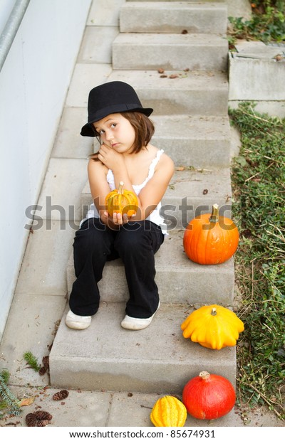 little, caucasian girl holding pumpkin in her hands