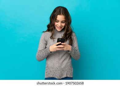 Little caucasian girl isolated on blue background sending a message with the mobile