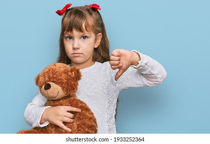 Little caucasian girl kid hugging teddy bear stuffed animal with angry face, negative sign showing dislike with thumbs down, rejection concept