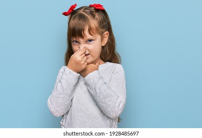 Little caucasian girl kid wearing casual clothes smelling something stinky and disgusting, intolerable smell, holding breath with fingers on nose. bad smell