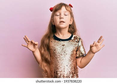 Little caucasian girl kid wearing festive sequins dress relax and smiling with eyes closed doing meditation gesture with fingers. yoga concept.