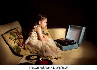 Little caucasian girl listening a single disk on the record player. Low key close-up photo