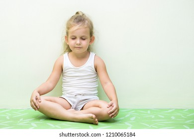 Little caucasian girl is making lotos pose in a yoga mat
