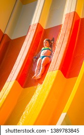 Little caucasian girl on water slide in the water park. Summer sunny day. Vacation and leisure activity concept