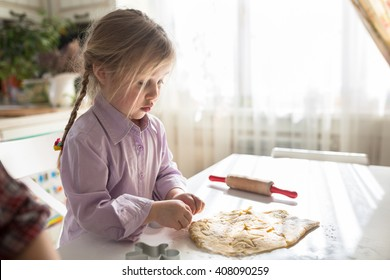 little Caucasian girl with pigtails makes the cookies from the dough, cutting out dough for cookies cute child,casual lifestyle photo series in real life interior