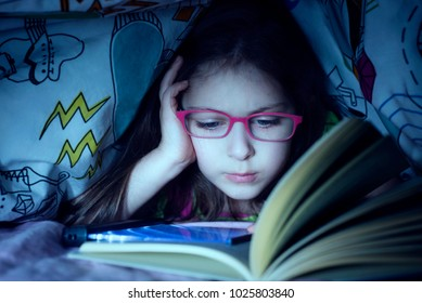 Little caucasian girl reading by stealth a book in the night under coverlet