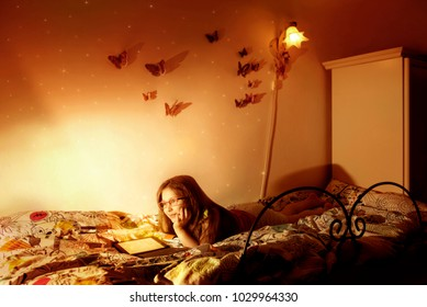 Little caucasian girl reading a e-book in the bed. Children, immagination and modern tecnology concept