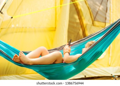 Little caucasian girl reading an e-book in hammock with tent in background. Summer, recreation and touristic concept.