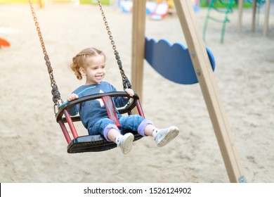 Little Caucasian girl riding swing at playground sunny summer day. European child having fun outdoor. Family leisure on park. Funny child enjoy summertime.